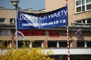 Na maszcie na flagę państwową powieszono banner reklamowy promujący dzień otwarty miejskiej szkoły.