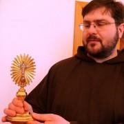 Ojciec Adam prezentuje relikwiarz z niewielkim kawałkiem drzewa krzyża, na którym skonał Jezus.