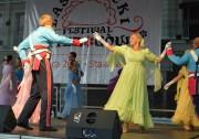 Elżbieta Żurawska w zielonkawej sukni tańczy poloneza na scenie na II Lasowiackim Festiwalu Pierogów w Stalowej Woli.
