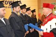 Prorektor profesor Jarosław Sęp wręcza absolwentom dyplomy ukończenia studiów inżynierskich.